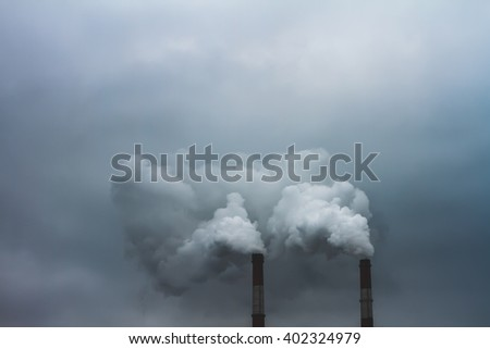 Steam and smoke is formed from boiler and turbine house at sunset. This boiler is a part of the thermal plant power in the industrial zone. The theme of global warming and environmental pollution.