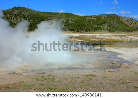 Steam as a geyser erupts in Yellowstone National Park, Wyoming, USA. - stock photo