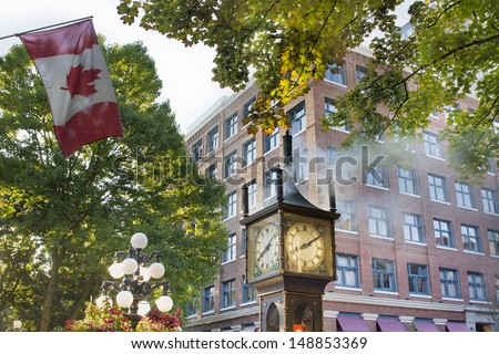 Steam Clock at Gastown Vancouver BC Canada with Canada Flag in the Morning with Sunlight - stock photo