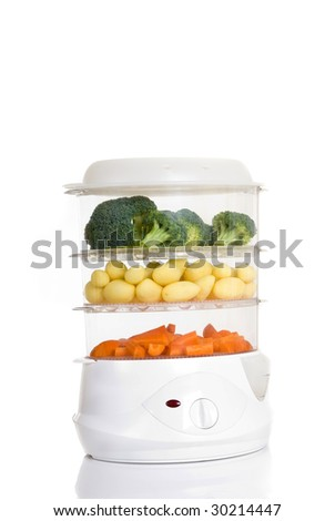 Steam cooker filled with fresh potatoes, broccoli and carrots, white background, reflective surface, studio shot - stock photo