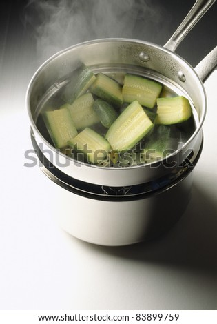 Steam-cooking the zucchinis - stock photo