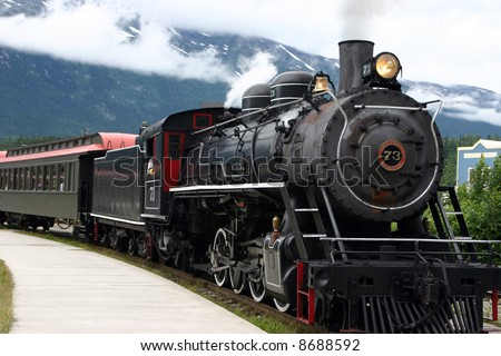steam engine train leaving the station full of tourists - stock photo
