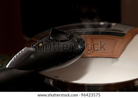 Steam escaping from lid of pressure cooker with reflection of modern kitchen - stock photo