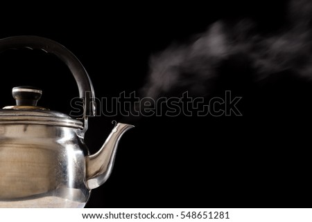Steam from boiling water in teapot on black background, empty space for text