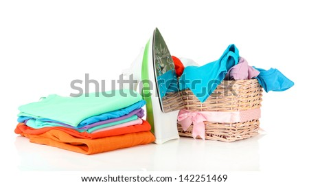 Steam iron and wicker basket with clothes, isolated on white - stock photo
