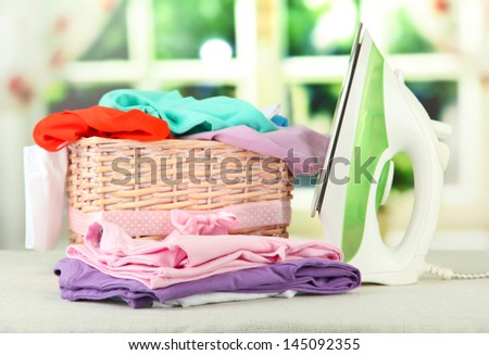 Steam iron and wicker basket with clothes, on bright background - stock photo