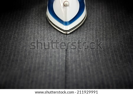 Steam iron on men's suit. - stock photo