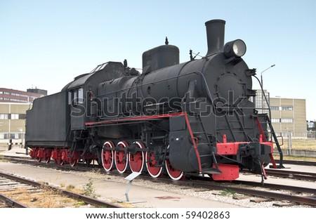 Steam locomotive beside a railway station platform. Retro train. - stock photo