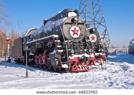 Steam locomotive beside a railway station platform. Winter. Retro train. - stock photo