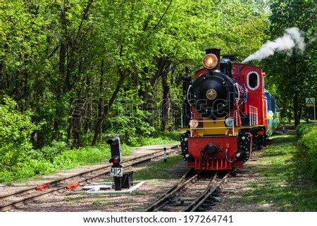 Steam locomotive going through the park and blowing off the steam out of the whistle - stock photo