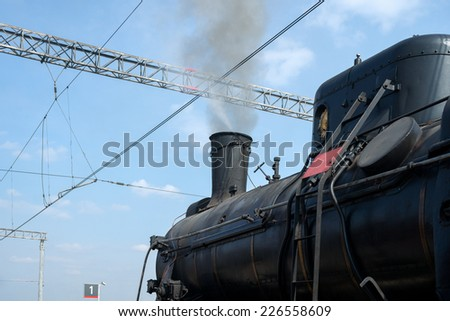 Steam locomotive in steam and ready to depart. Partial view of black boiler and chimney. Smoke comes out of a chimney. Wires and masts of the railway station - stock photo