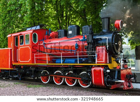 Steam locomotive with the smoke blowing off out of the smokestack. - stock photo