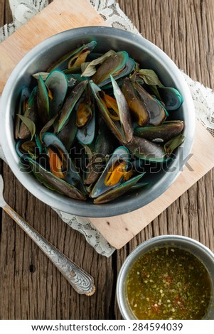 steam mussels with thai fresh herbs (basil, lemon grass, kaffir lime leaves) and seafood sauce on wooden background - stock photo