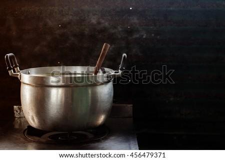 steam over cooking pot in kitchen on dark background - stock photo