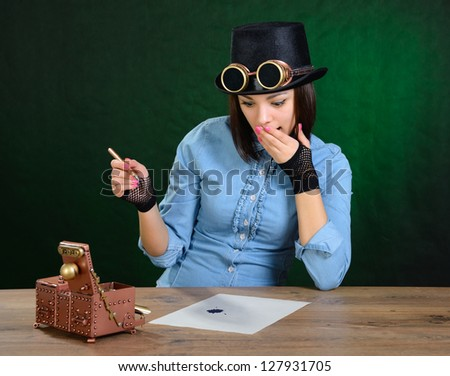 Steam punk girl tries calligraphy. - stock photo