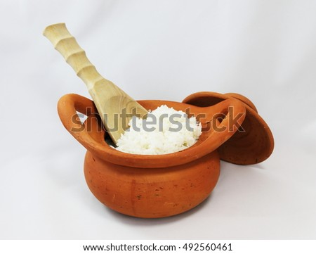 Steam rice in clay pot with wooden ladle