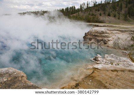 Steam rises from the now-defunct Excelsior Geyser in Yellowstone National Park, proving that it is still very much a geothermal hot spring. - stock photo