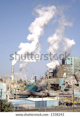Steam rises into the sky from the stacks of an industrial manufacturing complex - stock photo