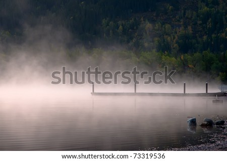 Steam rises on a mountain lake, near a boat dock.