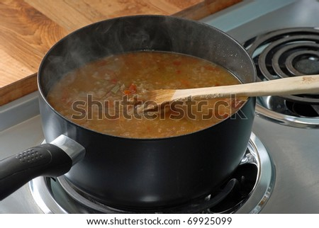 Steam rising from boiling pot of chicken and sausage gumbo. - stock photo