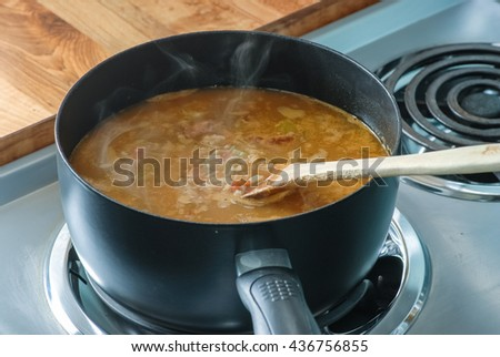 Steam rising from pot of gumbo boiling on electric range.  Spicy Cajun Food. - stock photo