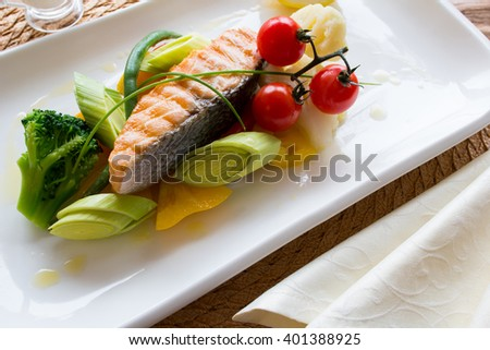 Steam salmon with a side dish of fresh vegetables on a white square plate. Top view - stock photo