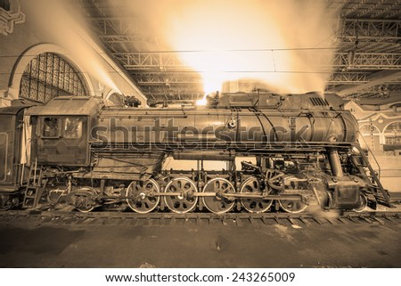 Steam train arrives to the station at night time. Vintage image. - stock photo