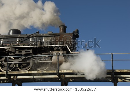 Steam train backing up on overhead bridge to load coal before taking a trip - stock photo
