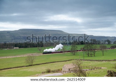 Steam train in Wensleydale with Penhill in view - stock photo