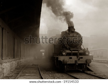 Steam train leaving bavarian village - stock photo