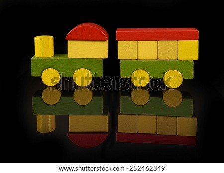 Steam train of wooden blocks, traditional toy on black background - stock photo