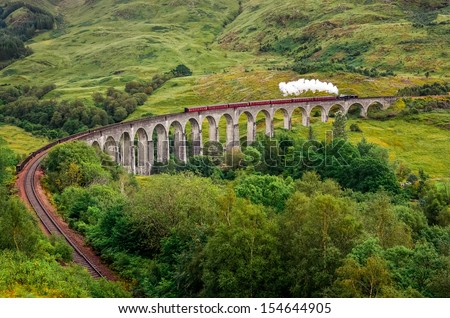Steam train on a famous Glenfinnan viaduct, Scotland, Great Britain - stock photo