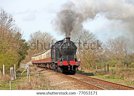 Steam train on a gentle day out with passengers on-board - stock photo