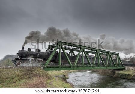 Steam train passes over an iron bridge - stock photo