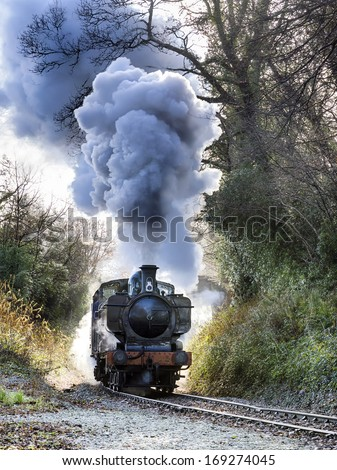 Steam train puffing along the tracks - stock photo
