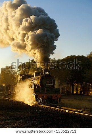 Steam train pulling out of the yard early morning in winter just as the sun is starting to rise - stock photo