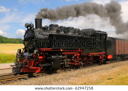Steam train with black smoke; island Rugen, Northern Germany - stock photo