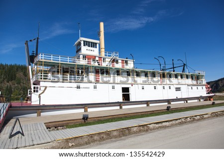 Steamboat docks on the banks of the Yukon River - stock photo
