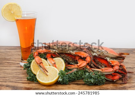 Steamed Blue Crabs garnished with kale and lemon slices and a glass of beer on a wooden table - stock photo