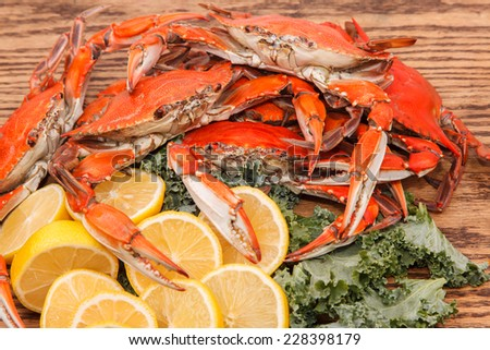 Steamed Blue Crabs, one of the symbols of Maryland State and Ocean City, MD with lemon slices and garnished with kale on a wooden table - stock photo