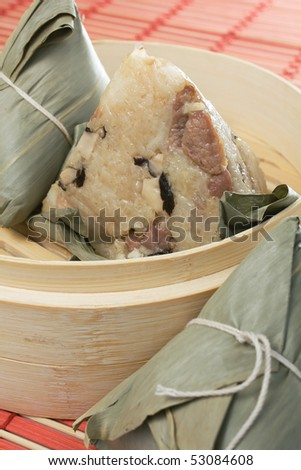 Steamed Chinese rice dumplings (zongzi) wrapped in bamboo leaves, filled with glutinous/sticky rice, pork, and mushrooms. These are eaten during the Dragon Boat Festival. - stock photo