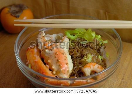 steamed crab with glass noodle on wooden background with chopsticks and persimmon fruit - stock photo