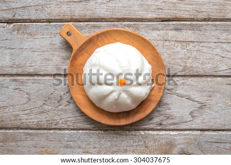 steamed dumpling in wooden dish on wooden table - stock photo