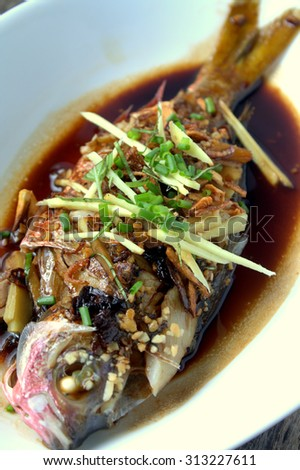 Steamed fish with soy sauce and herbs served in white dish