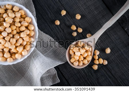 Steamed gold chickpeas in bowl on tablecloth with wooden spoon, tasty vegan food, top view, selective focus