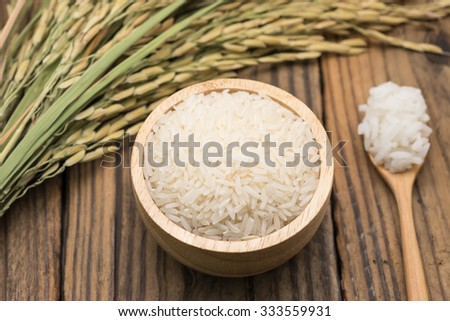 Steamed jasmine rice with uncooked grains and leafs with selective focused point - stock photo