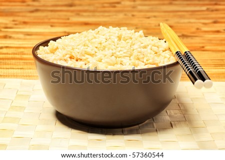 Steamed long rice in a brown bowl with chopsticks. - stock photo
