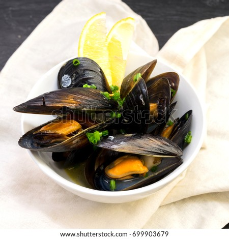 Steamed mussels in white wine with herbs and lemon. Seafood. Served in white bowl.