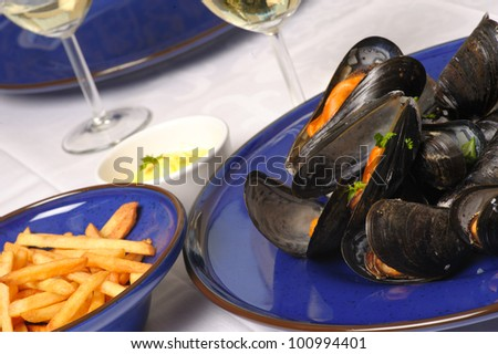 Steamed mussels with wine on blue plate  with french fries and mayonnaise and glasses of white wine