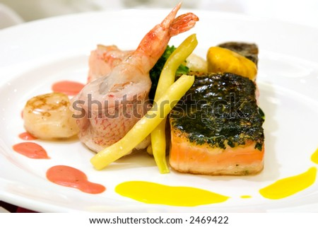 Steamed red snapper with shrimps. Fillet of salmon with crusted fine herbs and scallops. Crabmeat timbale served with baby vegetables and lobster sauce. - stock photo